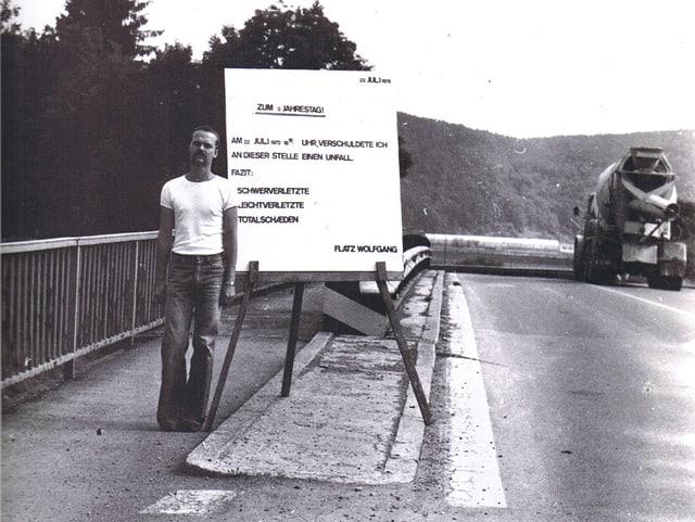 Schwarz-Weiss-Aufnahme: Flatz steht am Strassenrand neben einem Schild mit der Aufschrift «22. Juli 1975 zum 3. Jahrestag. Am 22. Juli 1972, 8.16 Uhr, verschuldete ich an dieser Stelle einen Unfall. Fazit: 3 Schwerverletzte, 2 Leichtverletzte, 2 Totalschäden. Flatz Wolfgang.»