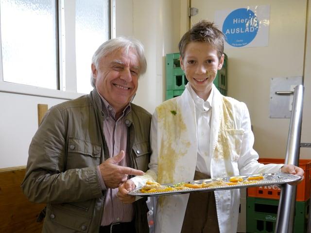 Emil Steinberger (links), kleiner Junge mit Tablett voller Essen (rechts)