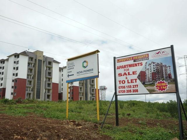 Verkaufschilder für Wohnungen vor neuen Gebäuden