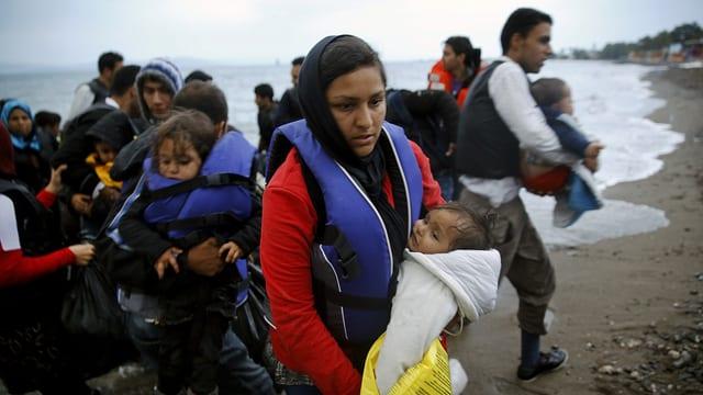 Frauen, Kinder und Männer an einem Strand, sie tragen Schwimmwesten.