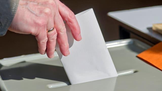 Hand wirft Wahlzettel in eine Urne