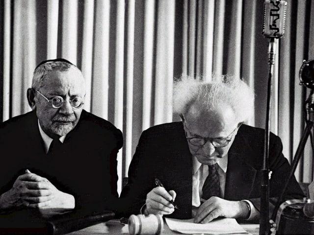 Zwei Personen sitzend an einem Tisch.