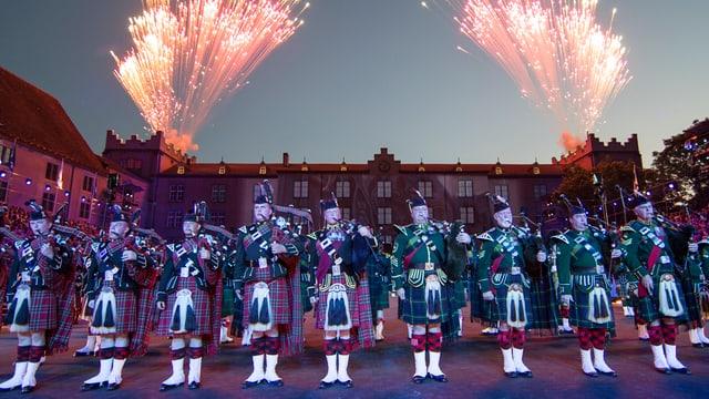 Soldaten in grüner schottischer Uniform spielen auf Dudelsäcken
