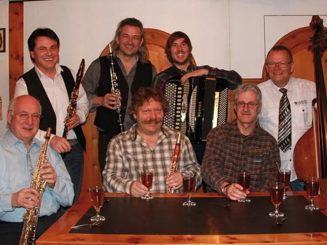 Gruppenfoto mit stehenden und sitzenden Musikern.