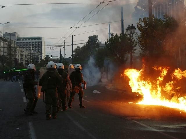 Ausschreitungen in Athen – Polizisten stehen auf einer Strasse neben Flammen.