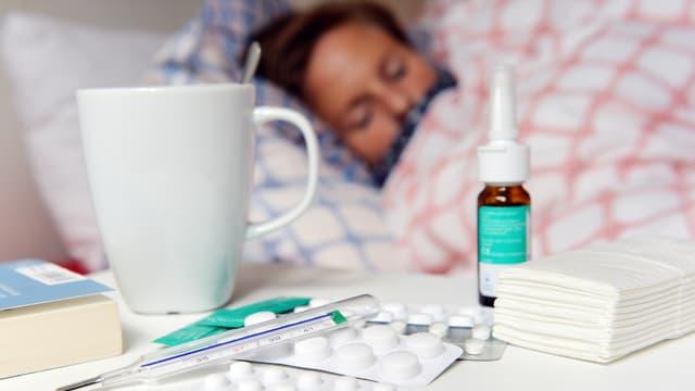 Person im Bett, im Vordergrund Medikamente und Teetasse.