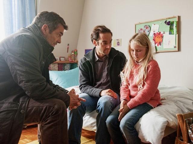 Filmszene: Julia sitzt auf dem Bett in ihrem Zimmer und blick zu Boden. Daneben sitzt ihr Vater, der sie anschaut. Gegenüber, auf einem Stuhl, sitzt Kommissar Flückiger.