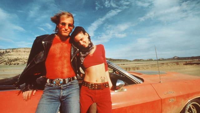 Ein Mann und eine Frau stehen in der Wüste vor ihrem roten Cabrio.