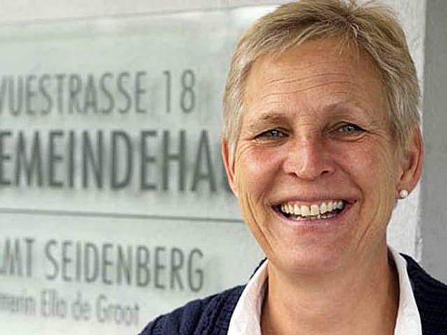 Portrtät der Pfarrerin vor dem Schild ihres Kirchgemeindehauses.