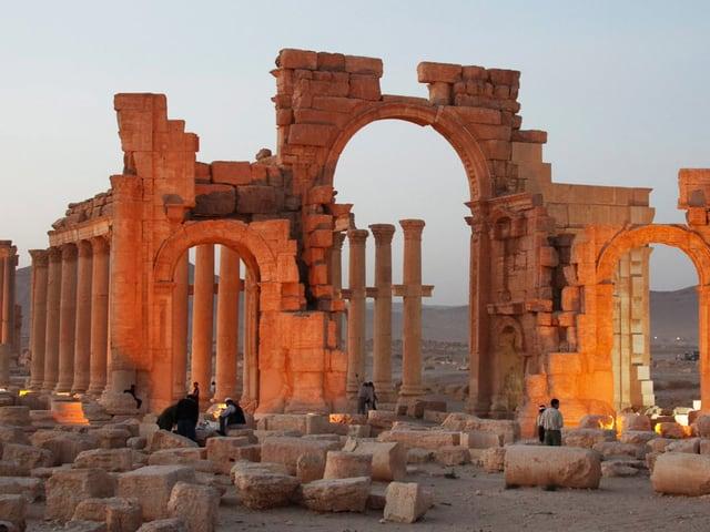 beleuchteter Torbogen in der Abenddämmerung. Der Weg ist nach dem Bogen von Säulen gesäumt.