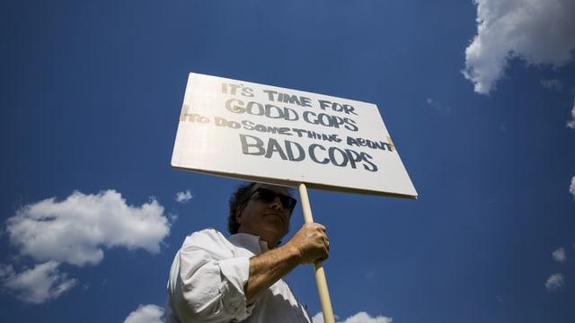 Demonstrant hält ein Schild in die Höhe.