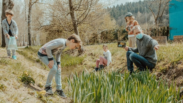ein Mann ist mit mehreren Kindern im Garten und erklärt etwas