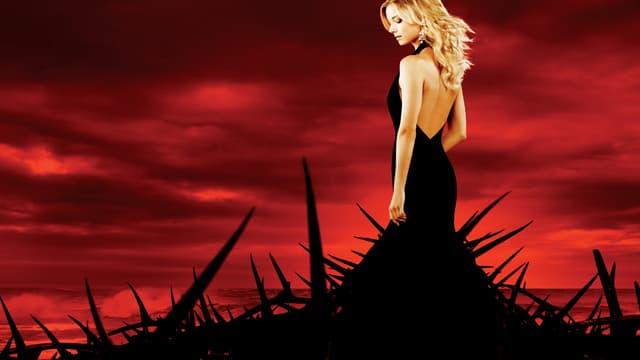 Symbolbild: Eine Frau steht in einem Dornenkleid vor dem blutroten Himmel.