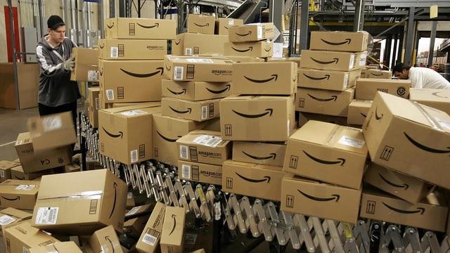 Ein Mann beim Sortieren eines Bergs Kartonschachteln, die als solche des Onlinehändlers Amazon zu erkennen sind.