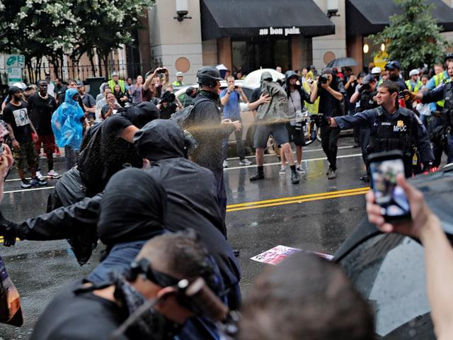 Ein Polizist schiesst mit einem Pfefferspray gegen einen Demonstranten.