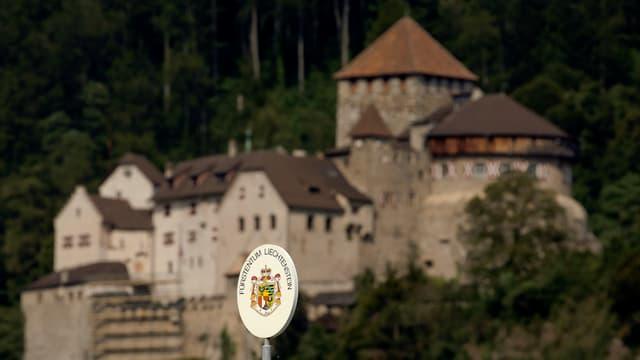 Ein Grenzschild an der Grenze zwischen der Schweiz und Liechtenstein, dahinter sieht man verschwommend den Fürstensitz.