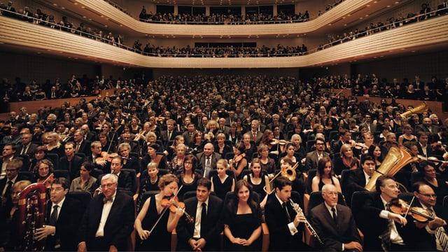 Blick in den grossen Saal des KKL Luzern, wo das Publikum und Orchestermitglieder mit ihren Instrumenten sitzen.