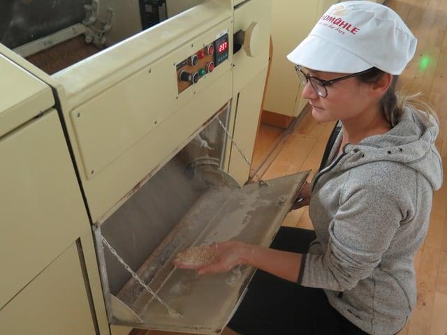 Frau hält Mehlprobe aus Maschine in der Hand