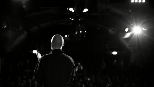 Mann mit Glatze auf Bühne, schwarz weiss