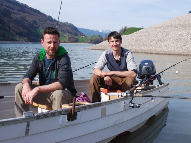 Nik Hartmann und Dominik Gasser am Angeln auf einem Boot.