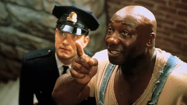 Filmszene: Blick von oben, ein grosser Mann zeigt mit dem Zeigefinger nach oben, ein kleinerer Polizist schaut in die gleiche Richtung.