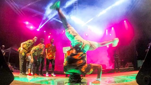 Ein junger Afrikaner vollführt auf einer Bühne einen Breakdance.