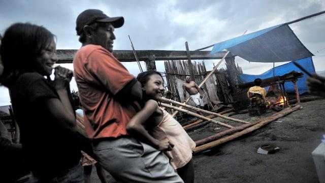 Ein Mann steht mit zwei Kindern vorne, im Hintergrund wird sein kaputtes Haus wieder aufgebaut.