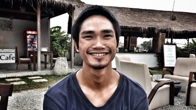 Ein junger Kambodschaner in blauem Pullover lächelt in die Kamera.