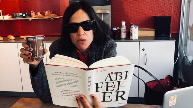 Annette König hat eine Sonnenbrille auf und liest in einem Take Away in «Abifeier». A