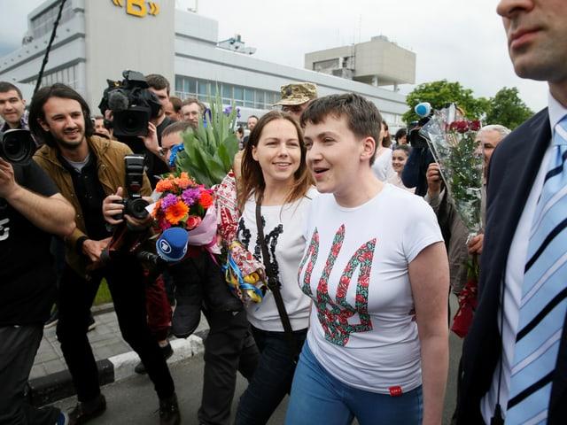Zwei Frauen, umlagert von Journalisten.