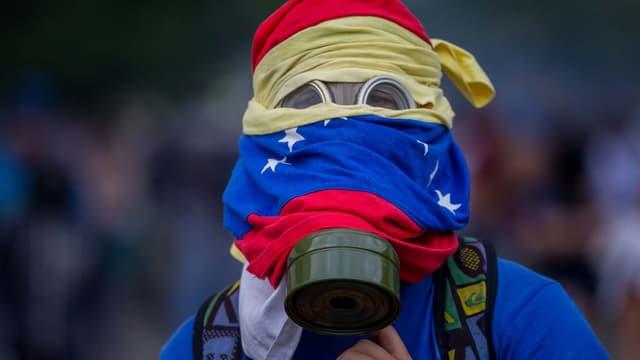Ein Demonstrant mit Gasmaske verhüllt sein Gesicht mit der Fahne Venezuelas.