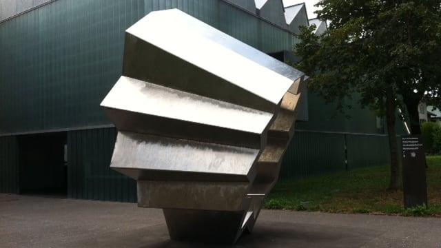 Eine kreisförmige Skulptur aus Stahl, dahinter ein modernes Haus aus Glas.