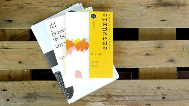 Drei Magazine liegen auf einer Holzpalette.