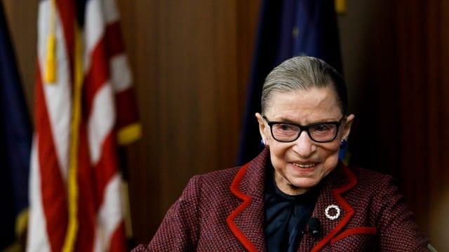 Ruth Bader-Ginsberg lächelt vor der US-Flagge