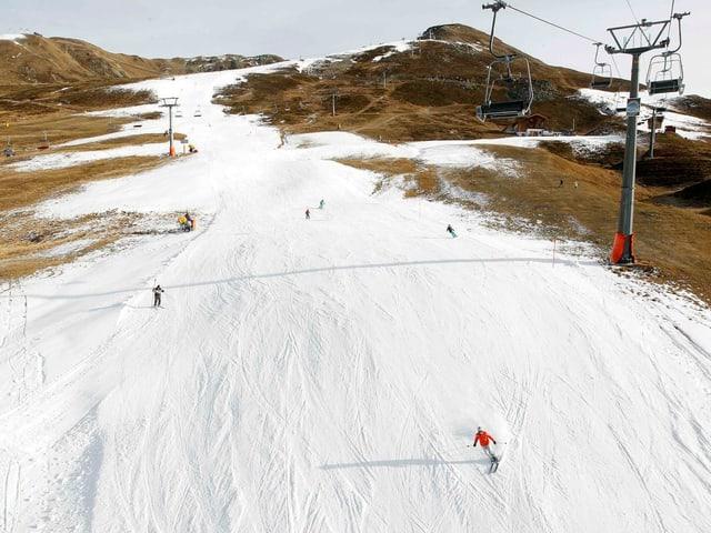 Skipiste in grün, eine Schneise ist beschniet und ein paar Wintersportler darauf unterwegs.