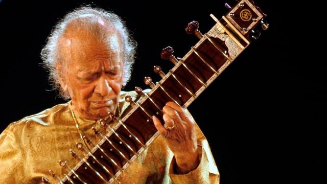 Der auf dem Bild von 2009 89-jährige Musiker trägt ein indisches, goldfarbenes Gewand und Goldschmuck und spielt, in sich versunken, auf einem Konzert in Kolkota.
