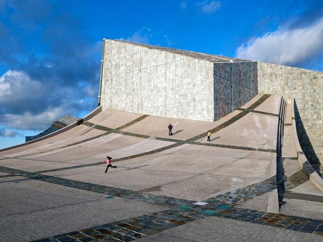 Kantiges, futuristisches Gebäude, zu dem sich der Boden anhebt