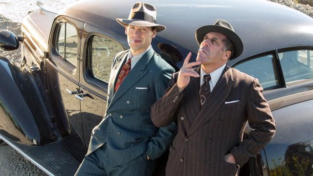 Zwei Männer in Anzug und Hut lehnen an ein Auto und rauchen.