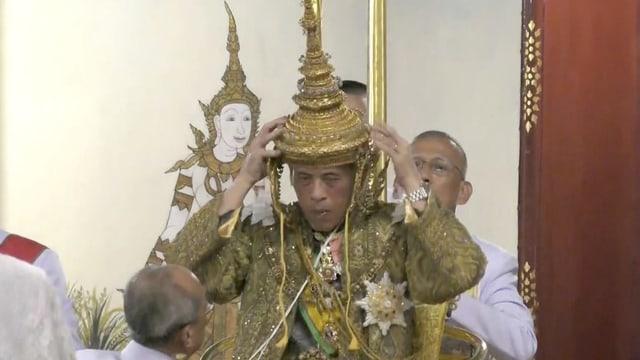 Mann setzt sich eine goldene Krone auf.