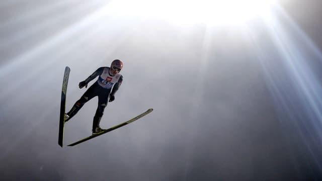 Ein Skispringer im Flug vor grellen Lichtstrahlen.