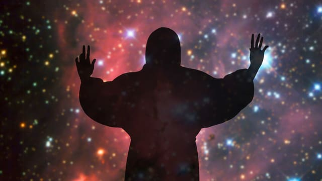 Eine Gottesfigur vor einem Weltallbild.