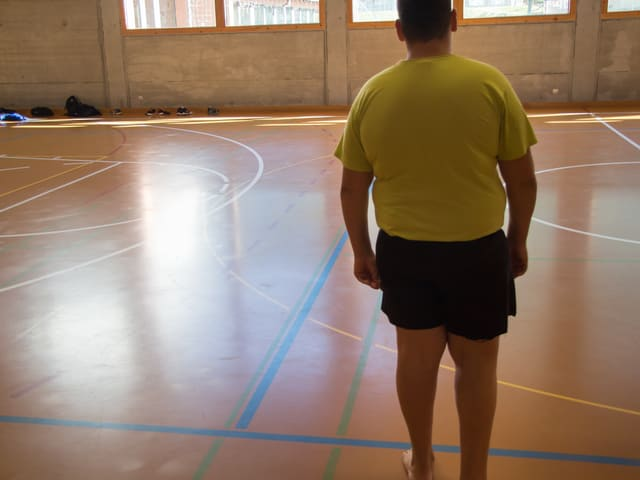 Khaled steht in einer Turnhalle. Man sieht ihn von hinten. Er hat deutliches Übergewicht.