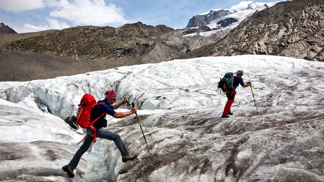 Zwei Wanderer auf dem Gornergletscher bei Zermatt. Einer springt über eine Spalte.