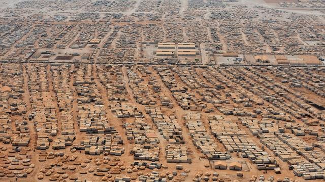 Tausende Zelte und Wohnwagen auf dem Wüstenboden.