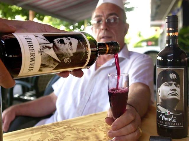 Ein Mann verkostet Wein aus Flaschen mit Hitler und Mussolini-Ettikett.