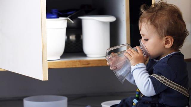 Kleiner Junge vor einem offenen Küchenschrank, leckt an einem Litermass.