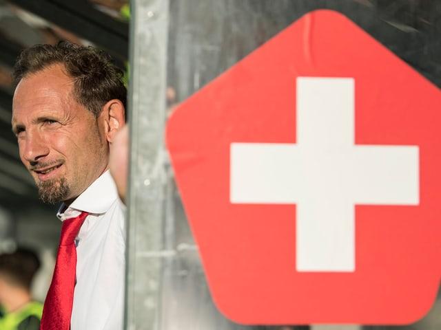 Mauro Lustrinelli steht vor der Trainerbank mit aufgeklebtem Schweizer Kreuz.