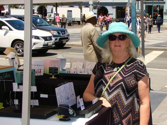 Eine Frau mit blauem Hut posiert neben einem Schmuckstand.
