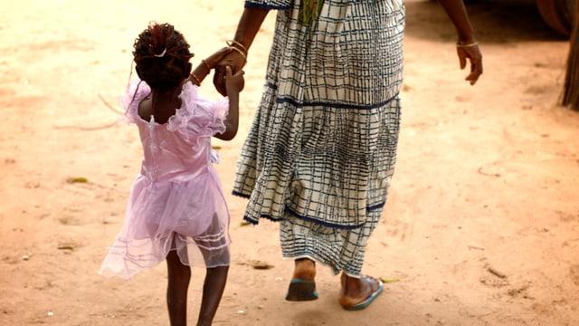 Frau in Afrika führt kleines Mädchen in rosa Kleidchen an der Hand.