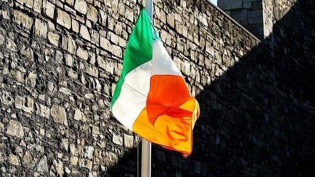 Eine irische Flagge vor einer Steinmauer.